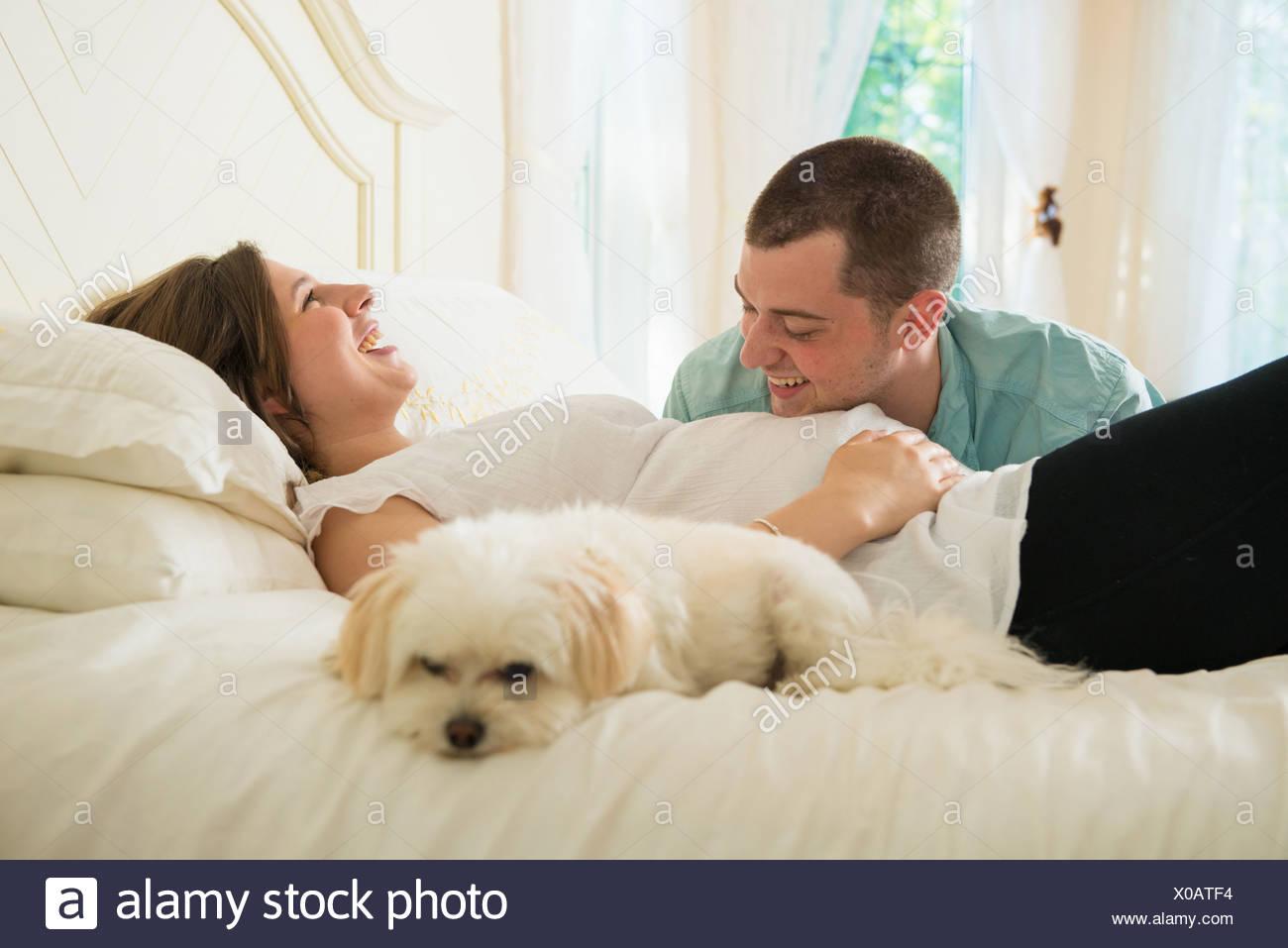 Schwangere Frau und Partner auf Bett liegend mit Hund Stockbild