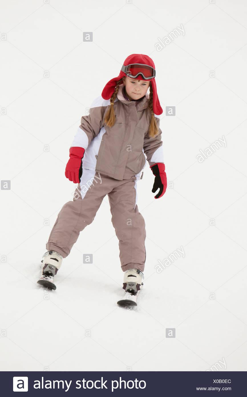 Junges Mädchen beim Skifahren Hang hinunter auf Urlaub In Bergen Stockbild