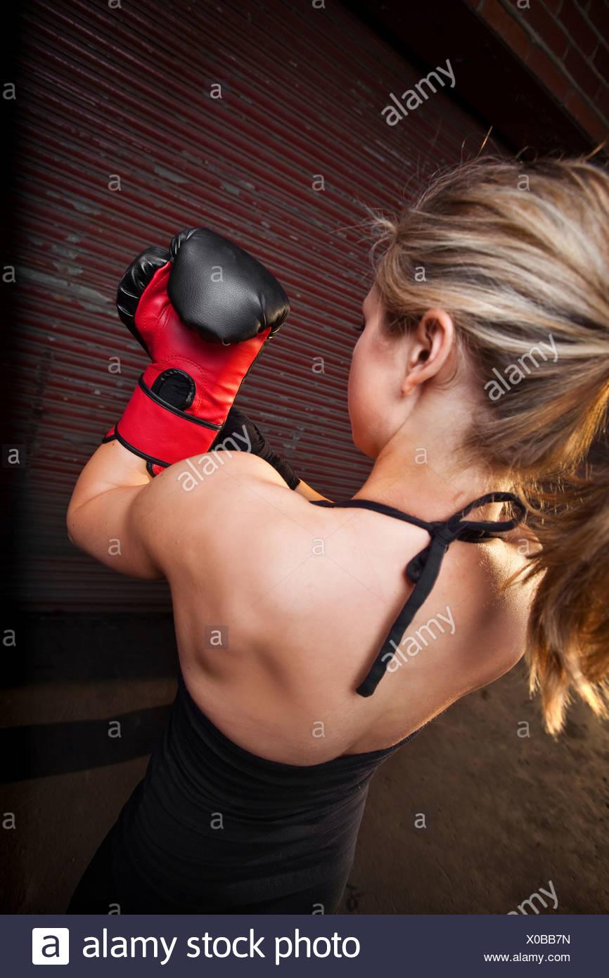 Ein junges Mädchen setzt auf ein Boxhandschuh vor dem Training für mixed Martial Arts außerhalb einer Lagerhalle in Birmingham, Alabama. Stockbild