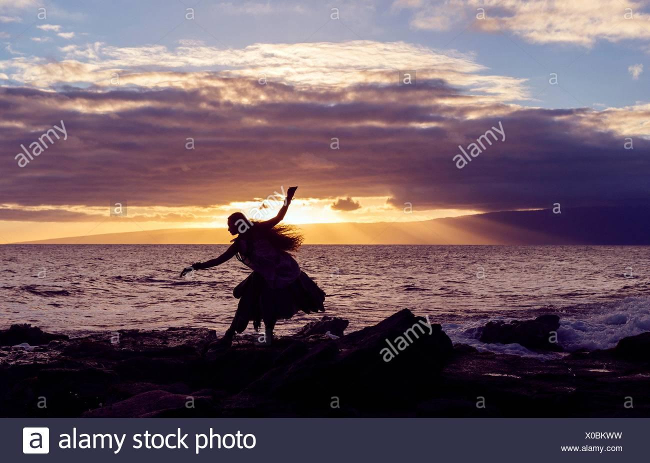 Silhouette Frau Hula tanzen auf Küstenfelsen tragen Tracht bei Sonnenuntergang, Maui, Hawaii, USA Stockbild