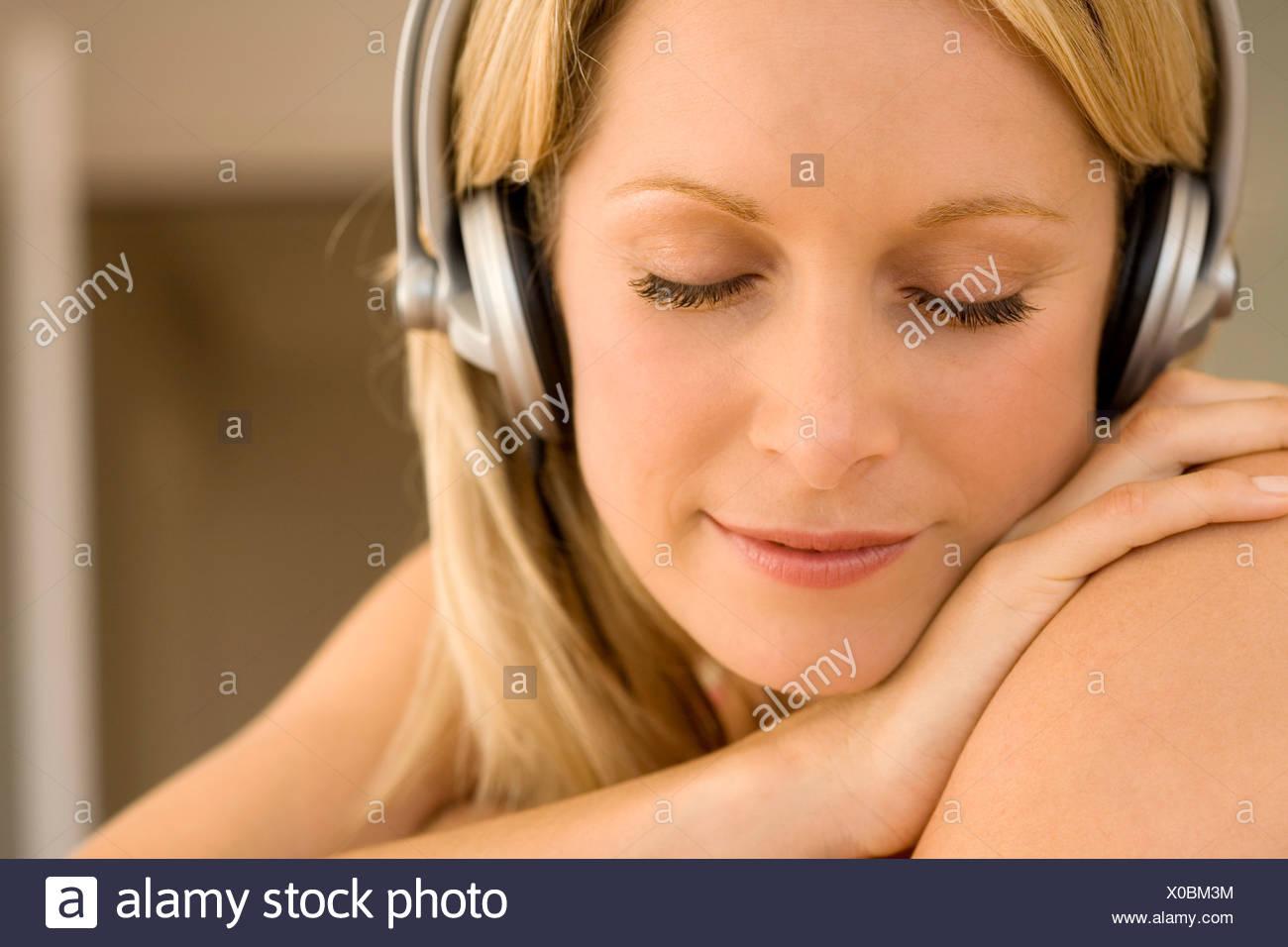 Junge Frau mit Kopfhörern Musik hören Stockbild