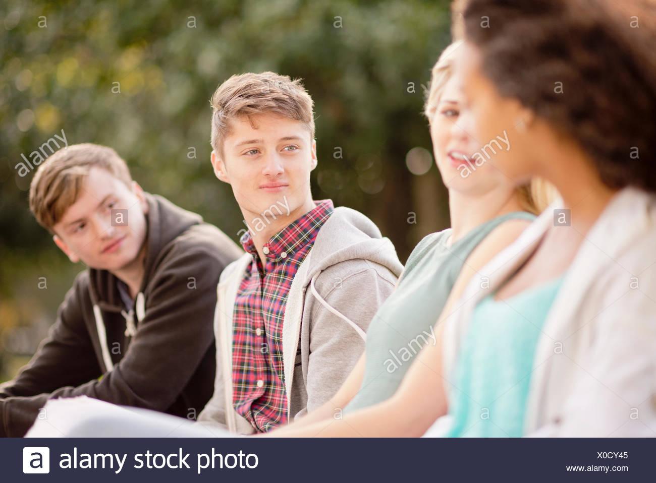 Vier junge Erwachsene Freunde chatten im park Stockbild