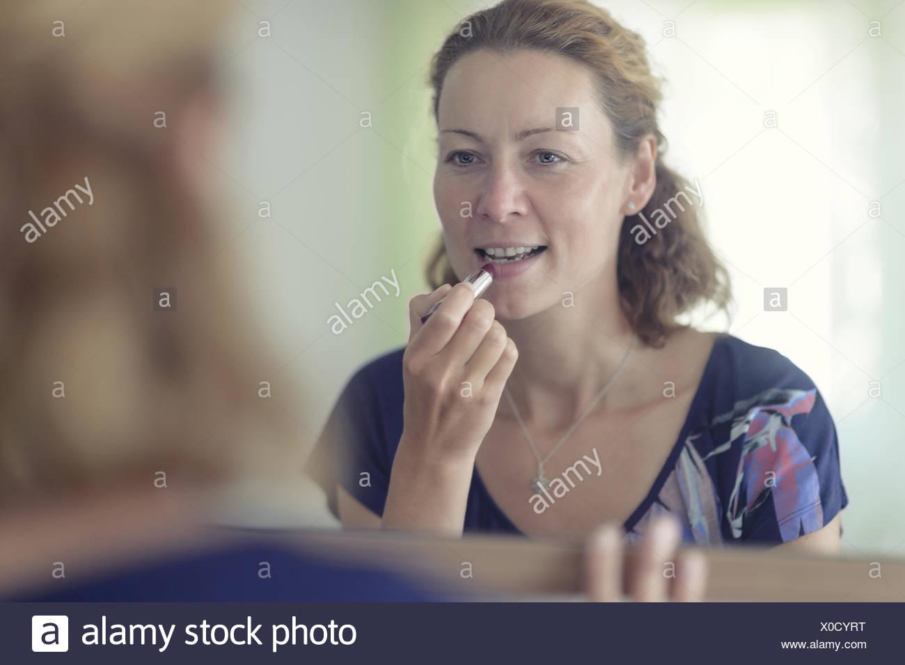 junge Frau steht vor dem Spiegel und Schmerzen Stockbild