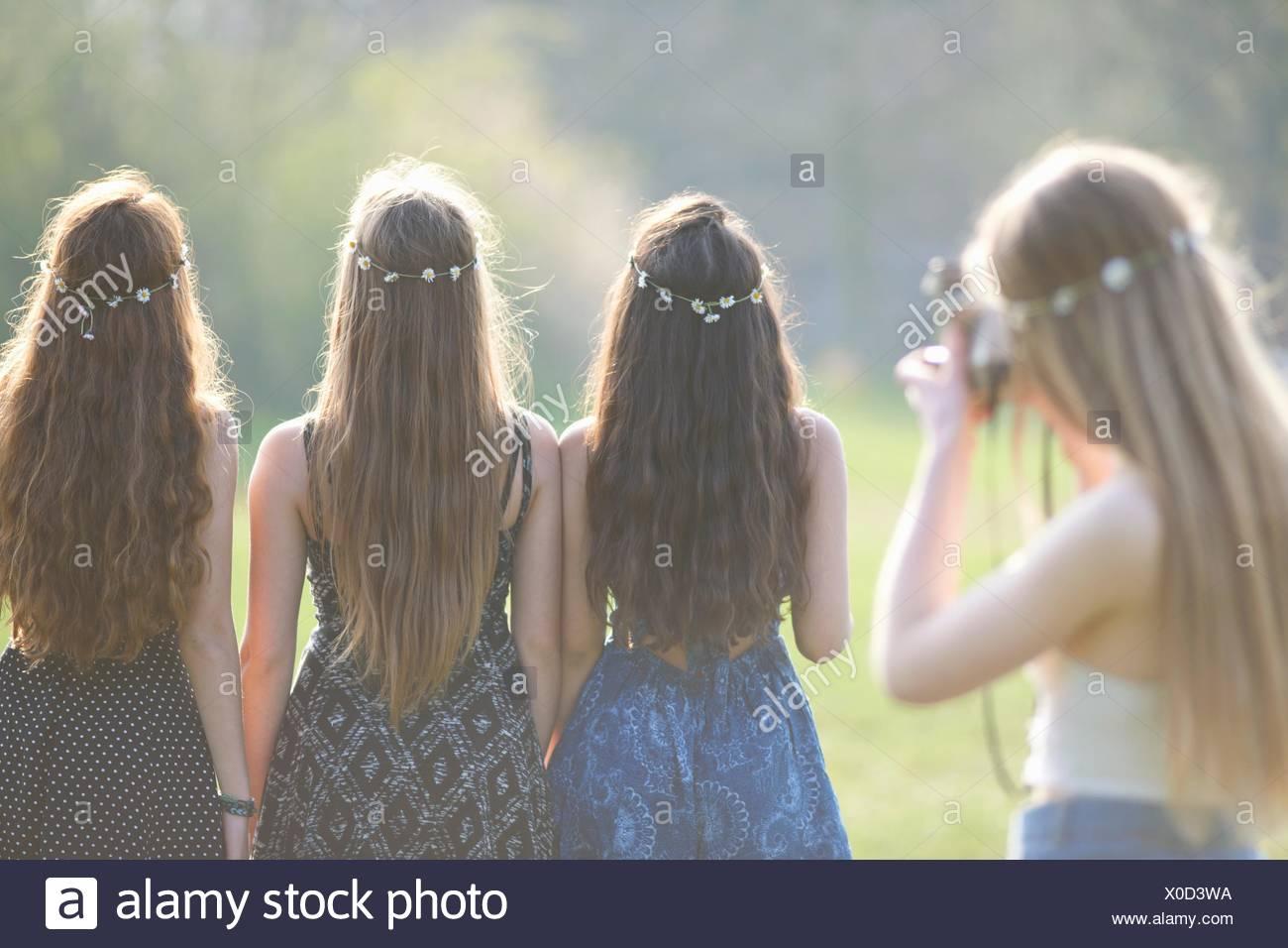 Rückansicht des Teenager-Mädchen fotografieren Freunde tragen Daisy-Chain Kopfschmuck im park Stockbild