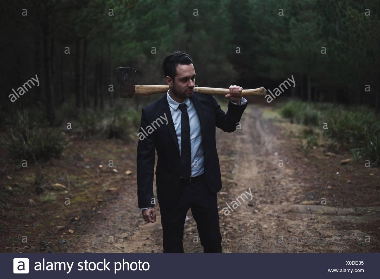 Junger Geschäftsmann mit Axt auf Feldweg im Wald stehen Stockbild