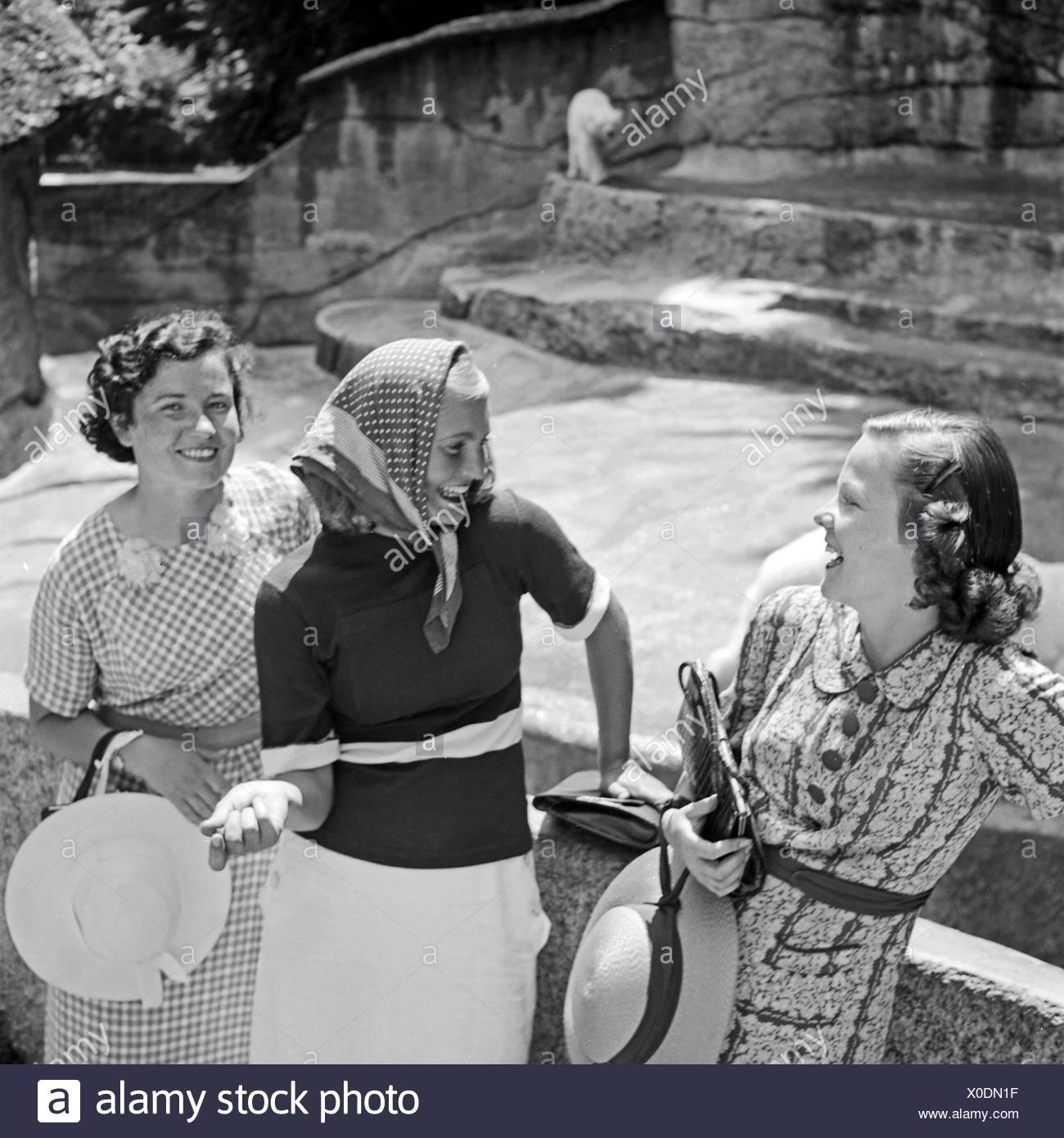 Drei Junge Frauen Stehen Beim Zoobesuich bin Eisbärgehege, 1930er Jahre Deutschland. Drei junge Frau besuchen ein Zoologischer Garten und sehen der Eisbär compound, Deutschland der 1930er Jahre. Stockbild
