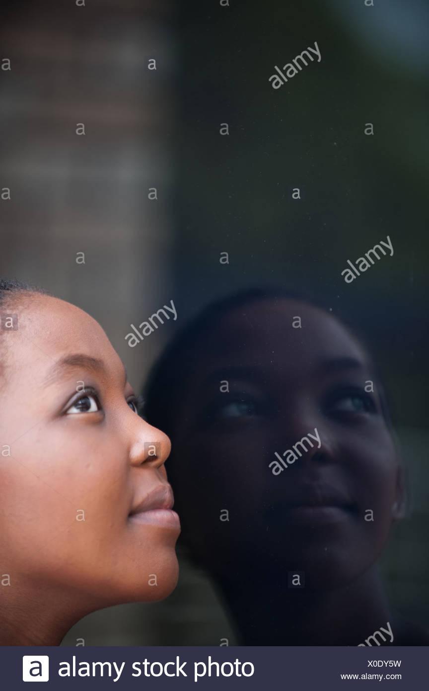 Junge Frau auf der Suche in Fenster mit Reflexion, Johannesburg, Provinz Gauteng, Südafrika Stockbild