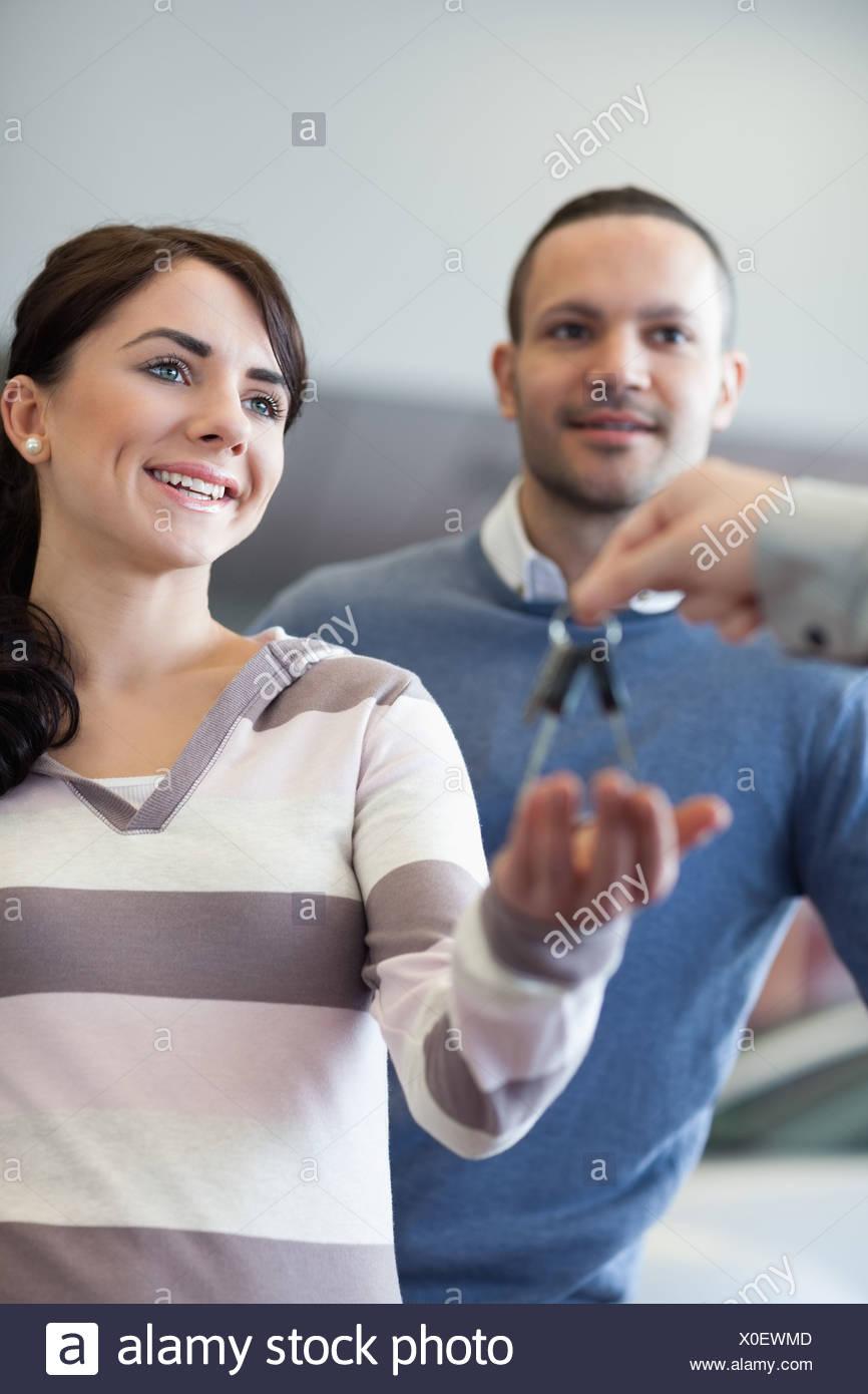 Paar, die Schlüsselübergabe von einem Autohändler Stockbild