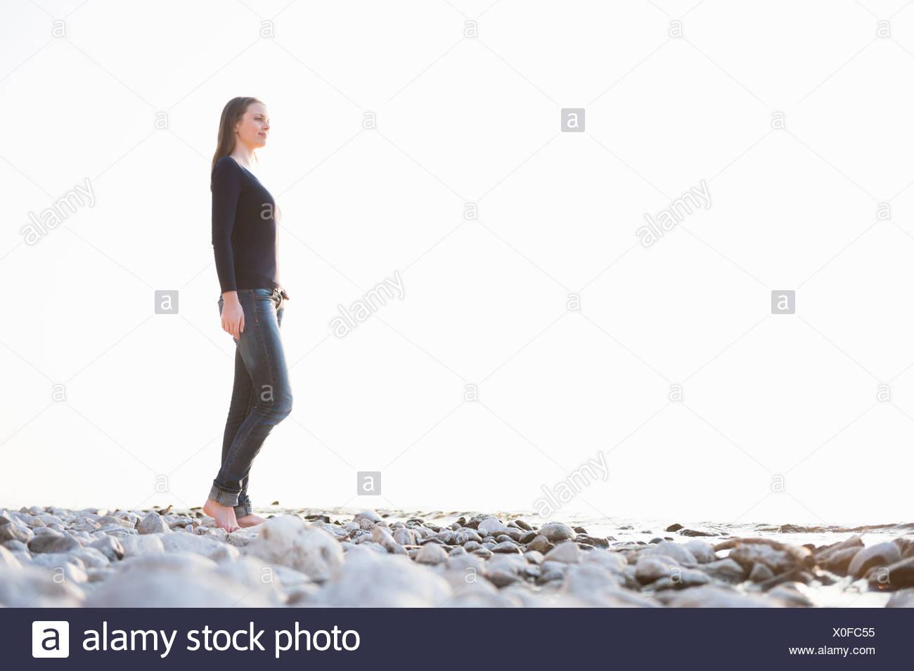 Junge Frau Spaziergang an der Küste Stockbild