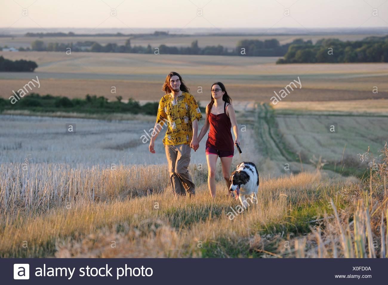 Paar der jungen Menschen zu Fuß mit einem Hund um Mittainville, Departement Yvelines, Region Ile-de-France, Frankreich, Europa. Stockbild