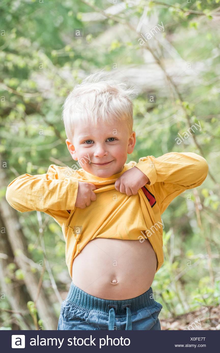 Lächelnde junge zeigt Bauch Stockbild