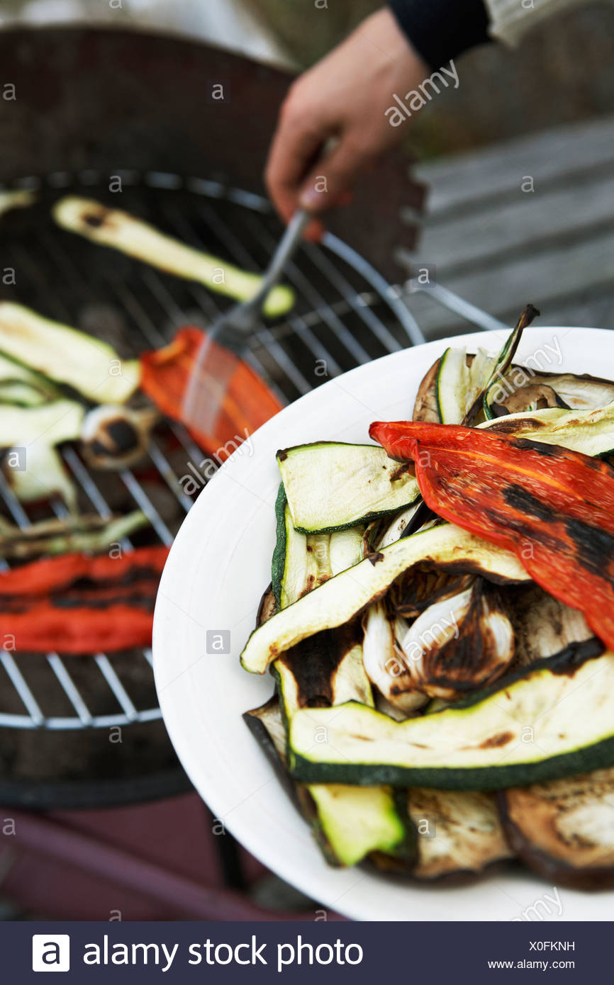Die Hand einer Person Gemüse grillen. Stockbild