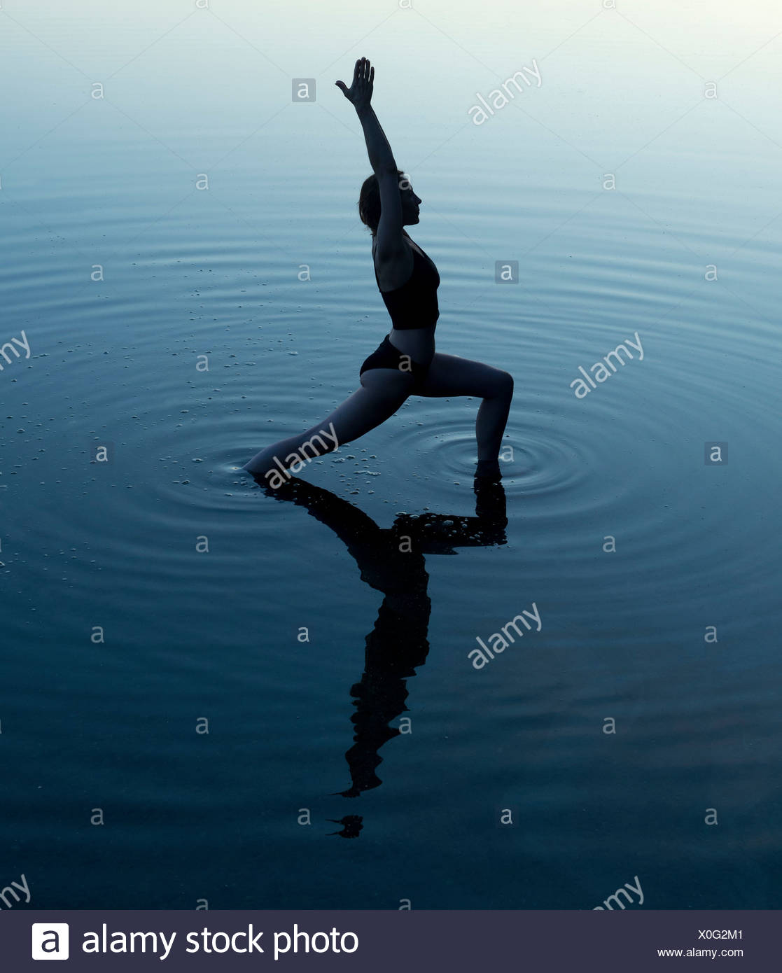 Frau in Yoga-Pose in See Stockbild