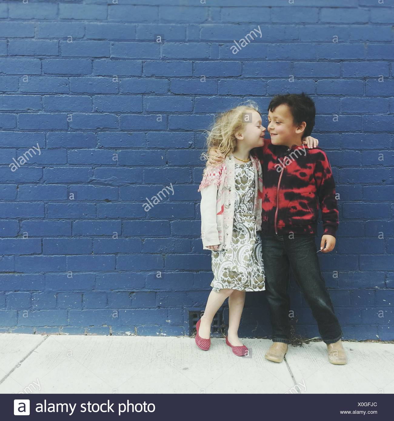 Jungen und Mädchen mit ihre Arme umeinander Stockbild