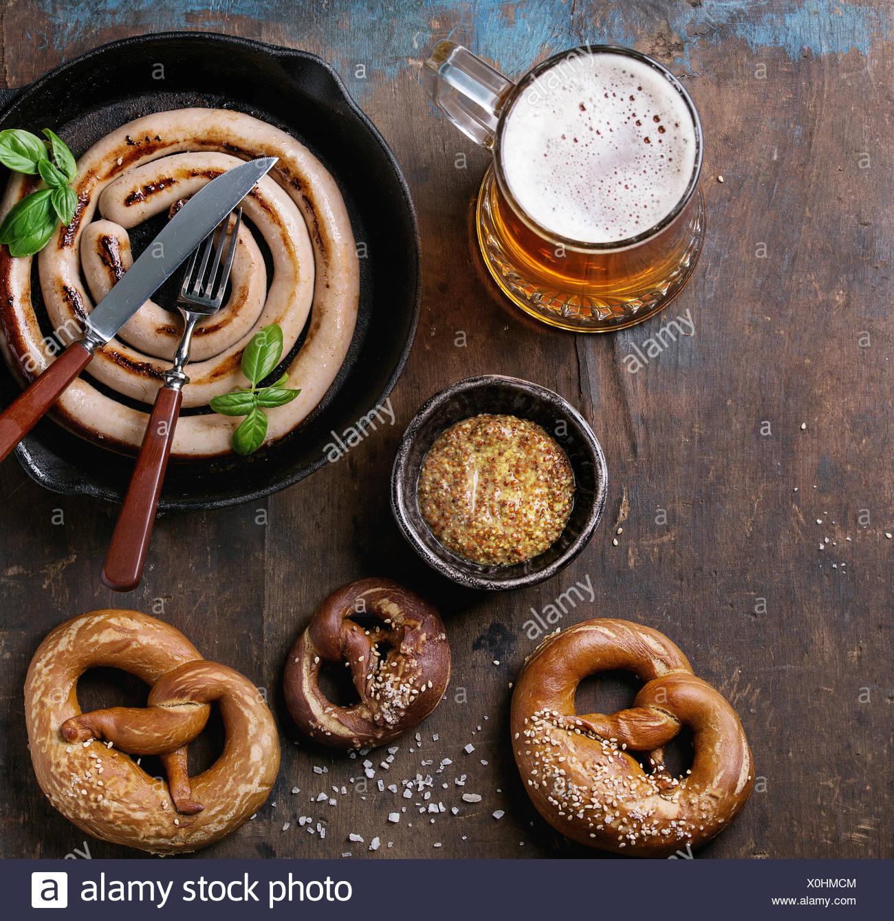 Lager-Bier mit Bratwurst in Pfanne mit Besteck und traditionellen gesalzenen Brezeln und Schüssel mit Senf über alte hölzerne dunklem Glas. Top vi Stockfoto