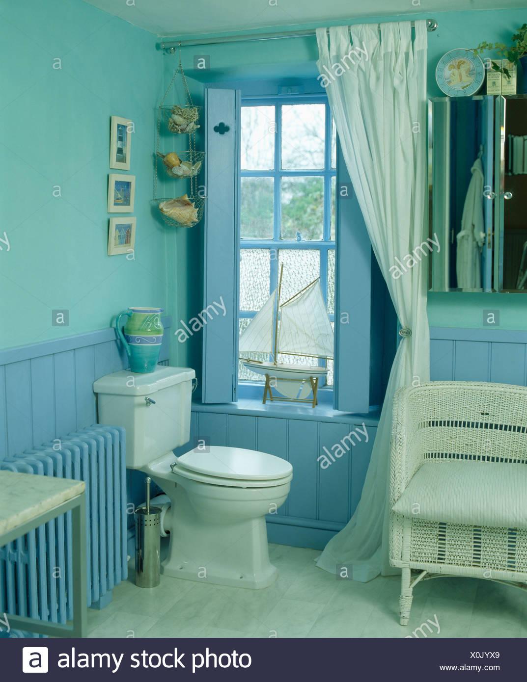 Cremefarbene Vorhang und blass blauen Fensterläden auf Fenster in ...