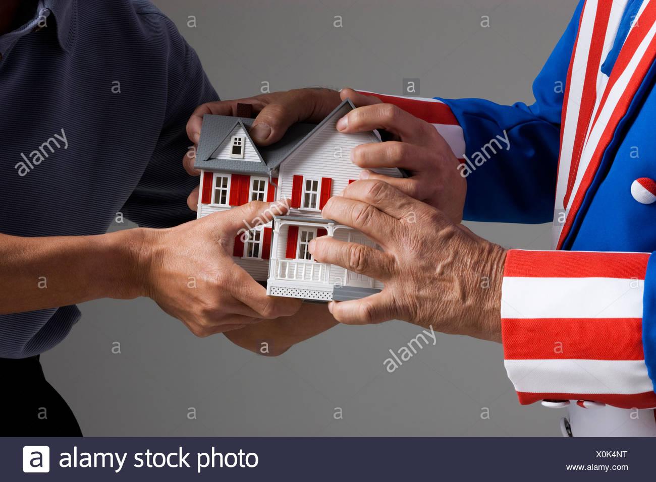 Zwei Männer ziehen Modus Haus in verschiedene Richtungen Stockbild