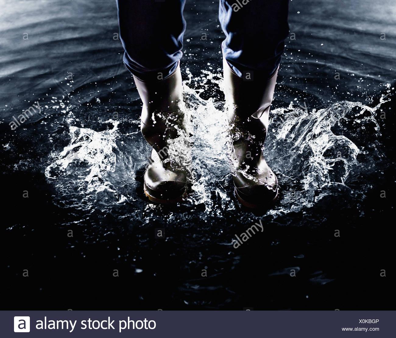 Gummistiefel, planschen im Wasser Stockbild
