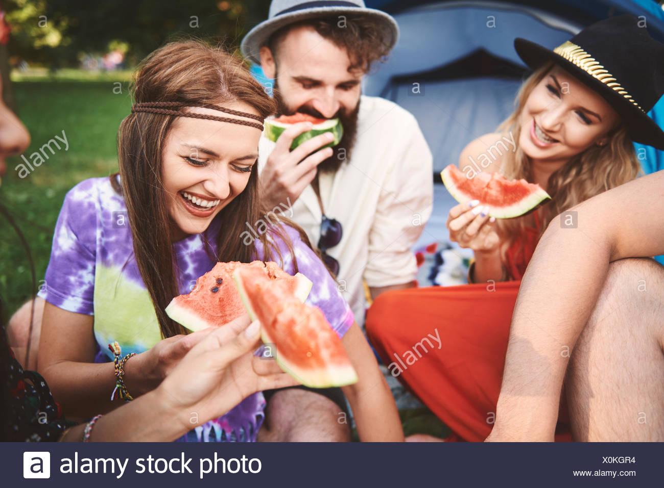 Junge boho erwachsenen Freunde essen Melone Schichten in der Festival Stockbild