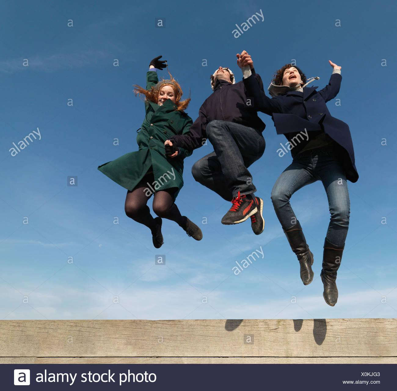 Freunde über hölzerne Hindernis springen Stockbild