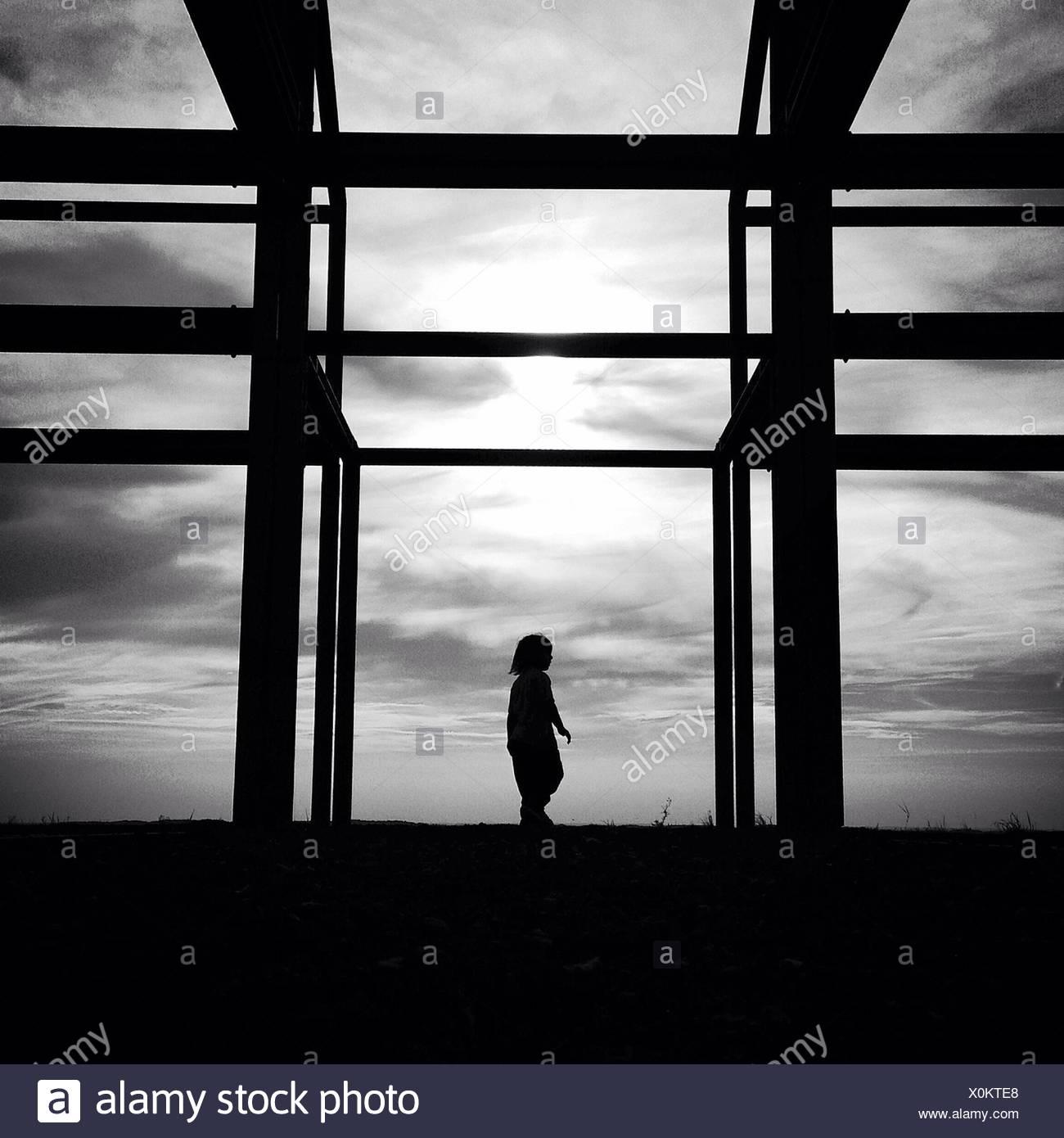Silhouette-Mädchen stehen im Niederdeutschen Hallhouse Rahmen gegen Himmel Stockbild