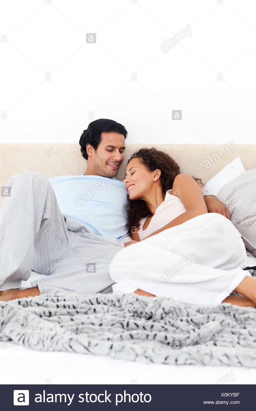 Leidenschaftliche Paare zusammen auf ihrem Bett liegend Stockbild