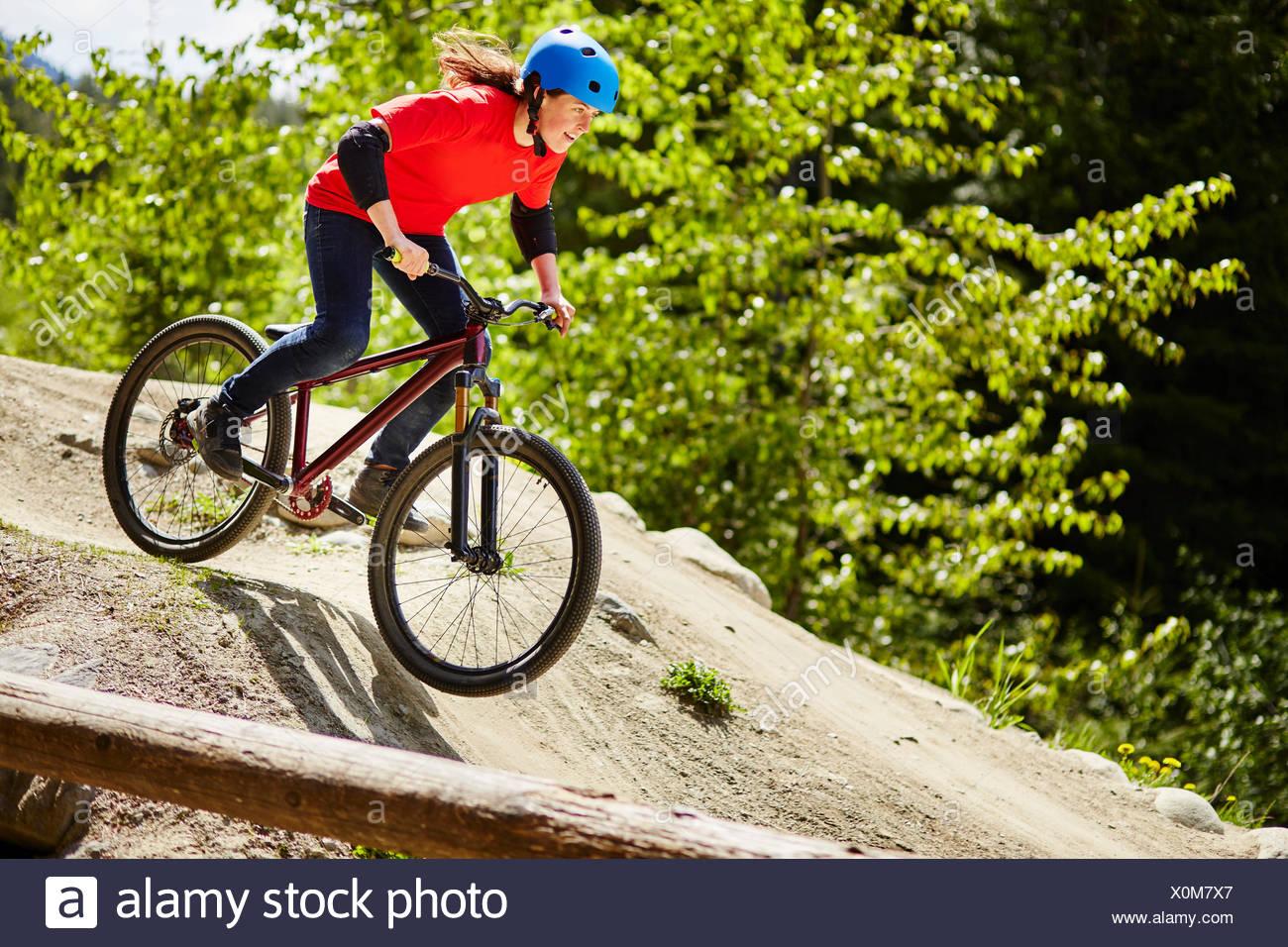 Junge weibliche bmx-Biker Beschleunigung nach unten Felsen im Wald Stockbild