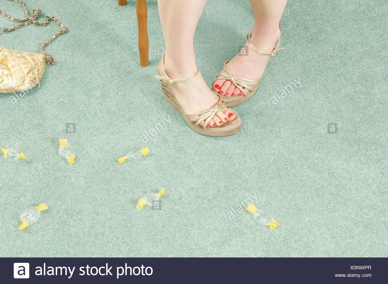 Frauenbeine mit Bonbonverpackungen Stockbild