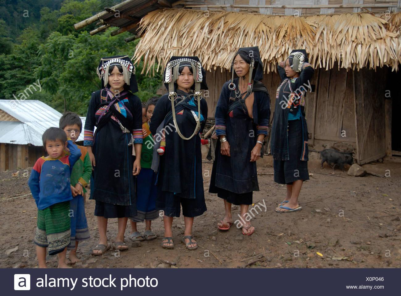 Vier Frauen des Stammes Akha Phixo in traditioneller Tracht mit Kindern, Ban Phapoun Mai, Provinz Phongsali, Laos, Süd-Ost Stockbild