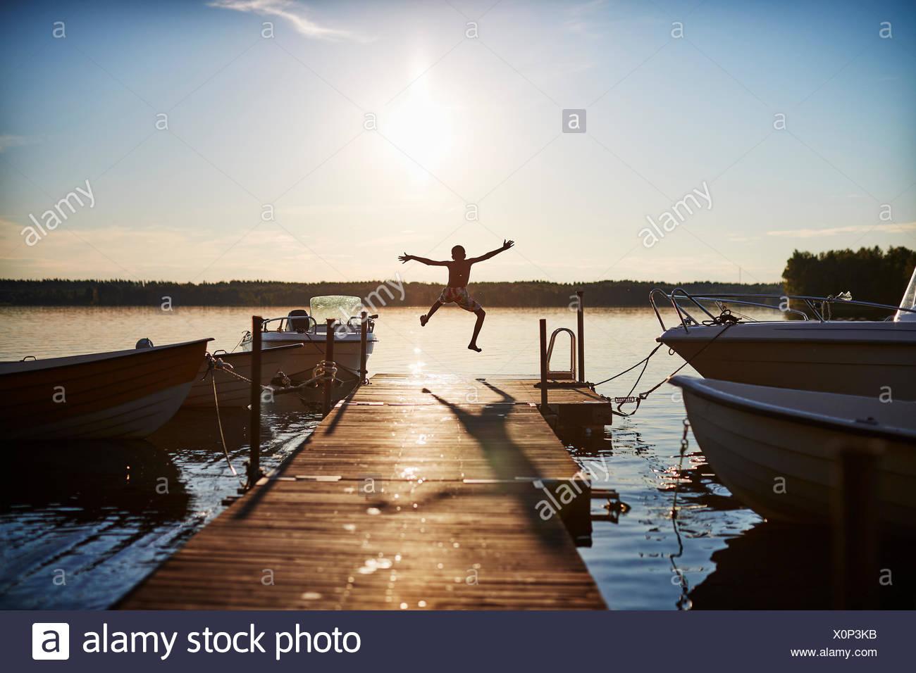 Junge springen auf einem Pier Stockbild