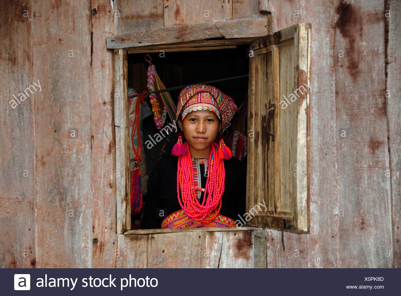 Junge Frau des Stammes Akha Pala Blick aus einem Fenster gekleidet in einem bunten Kopf-Kleid und eine rote Halskette, Ban Saenkham T Stockbild