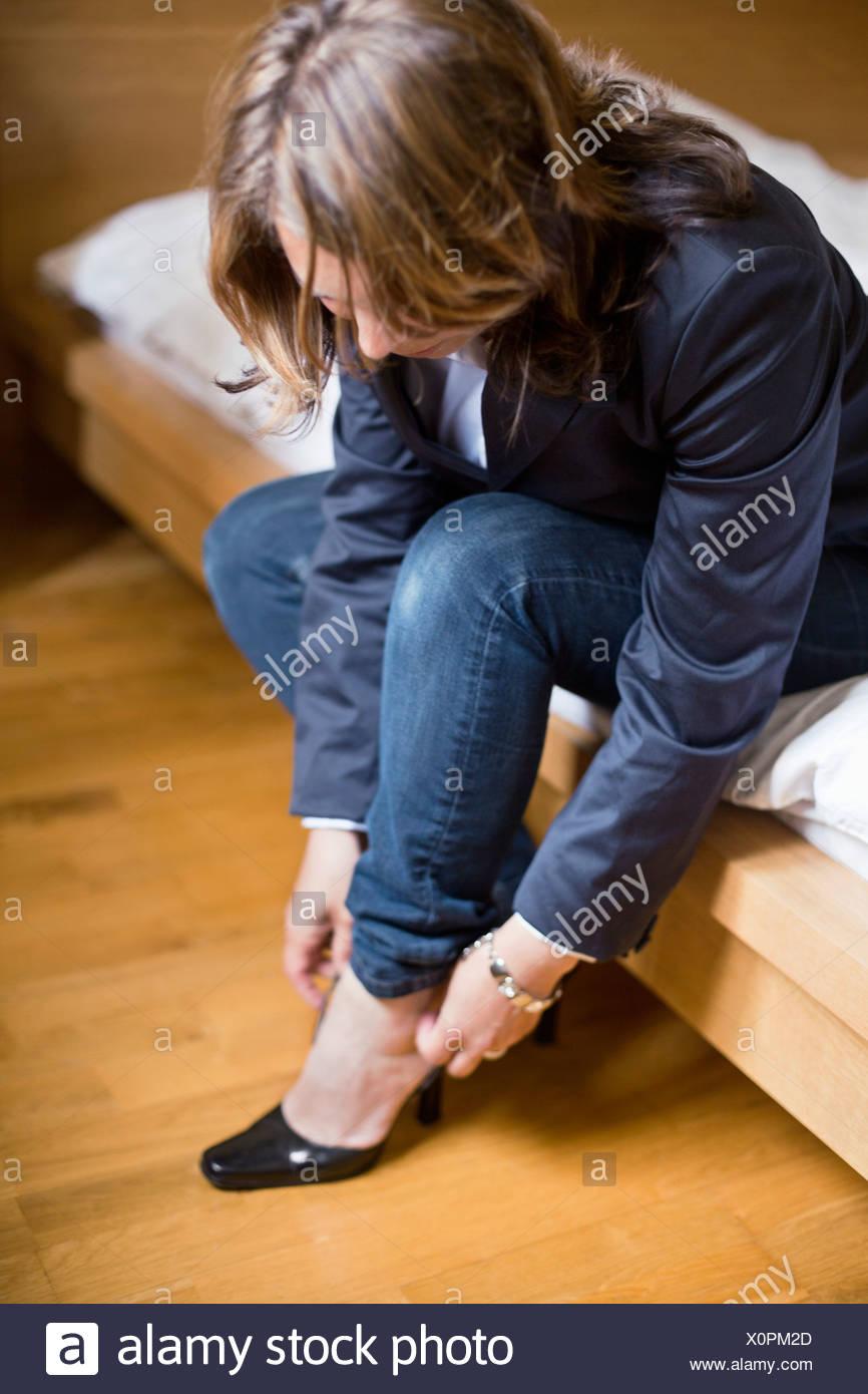 Frau legt auf Schuh Stockbild