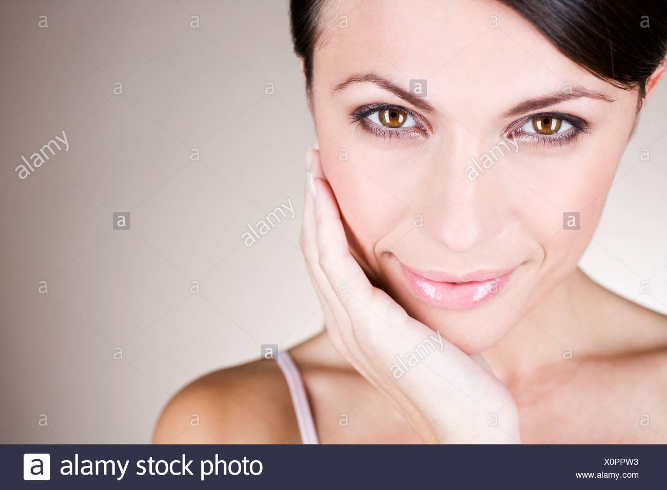 Porträt einer jungen Frau, ihr Gesicht zu berühren Stockbild