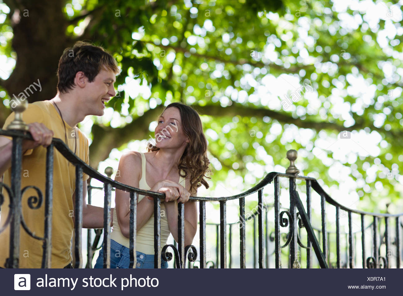 Lächelnde paar stützte sich auf Geländer im freien Stockbild