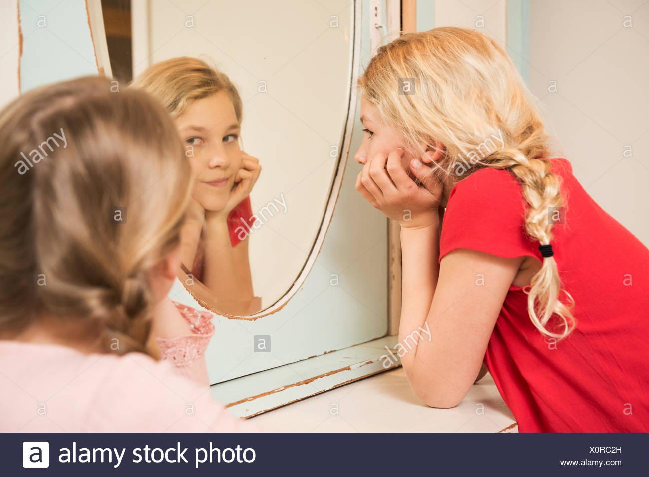 Mädchen starrte Schwester im Schlafzimmer Spiegel Stockbild