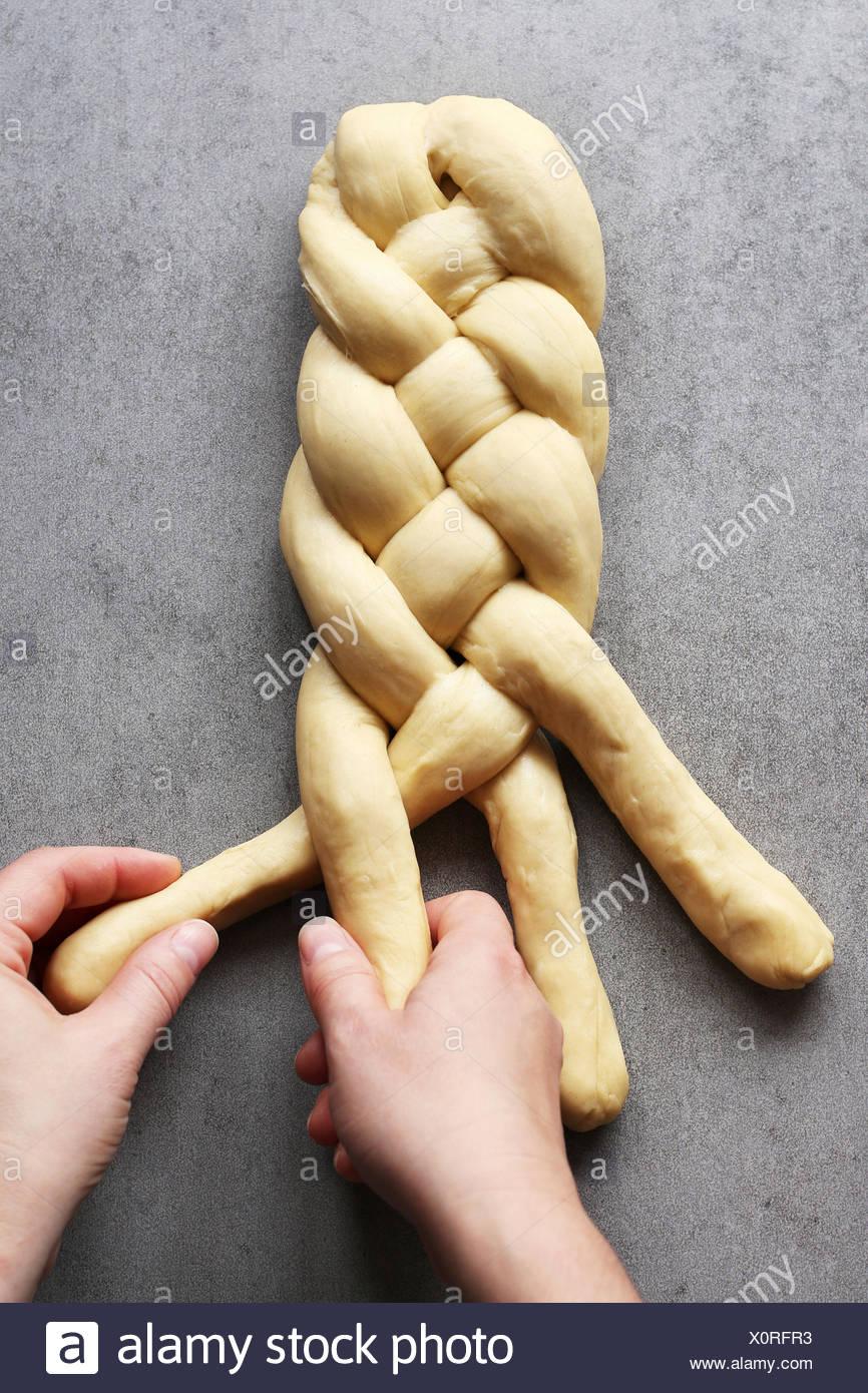 Weibliche Hände Flechten Challah Brotteig. Ansicht von oben Stockbild