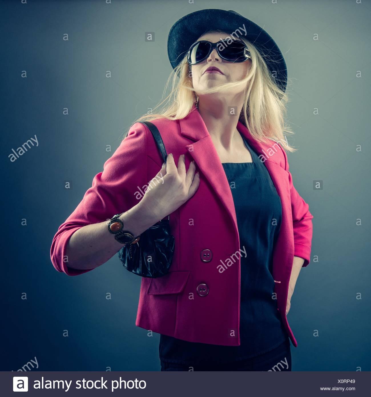 Urbane reife Frau das Tragen einer Sonnenbrille und Hut, Studio gedreht. Stockbild