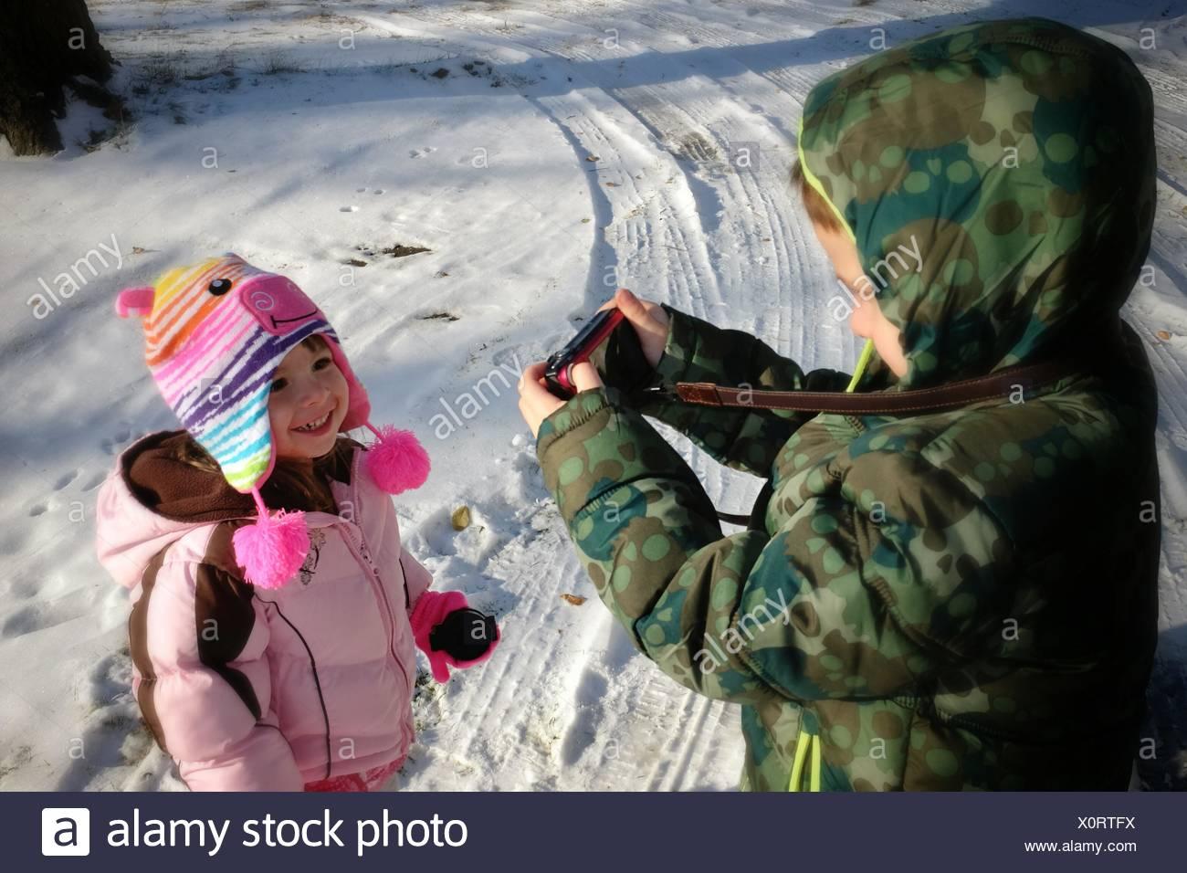 Bruder fotografieren Schwester auf Schnee bedeckt Feld Stockfoto