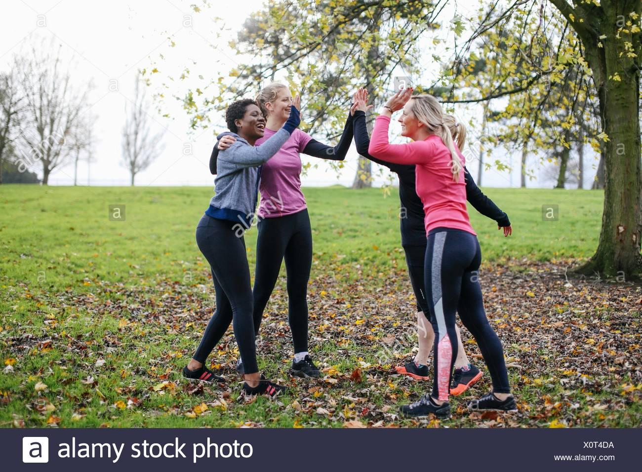 Frauen und Jugendliche vorbereiten, trainieren, geben einander ein high Five im park Stockbild