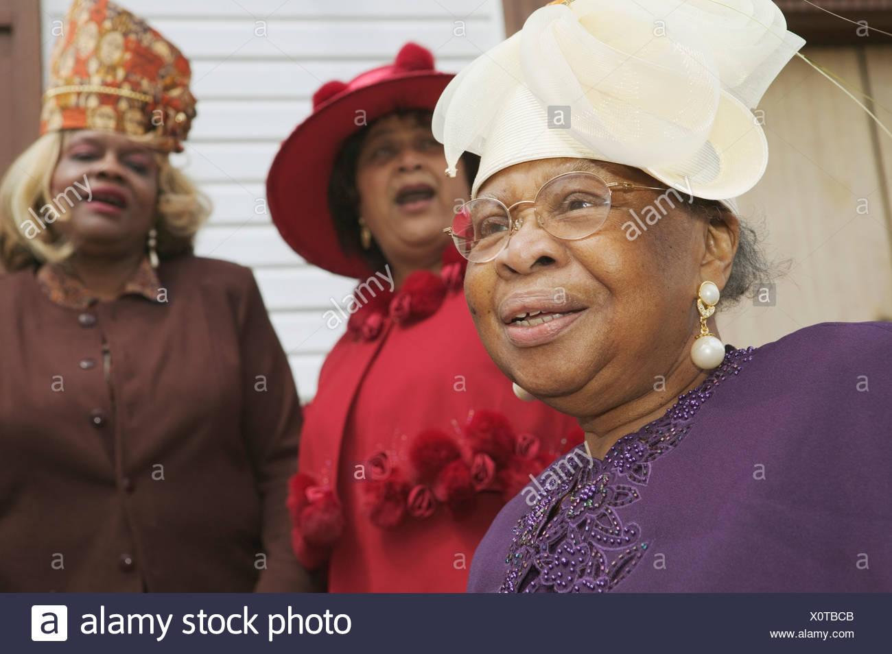 d1a4a102788f Drei Frauen in Führungspositionen in feine Kleider und ausgefallene Hüte  Stockbild
