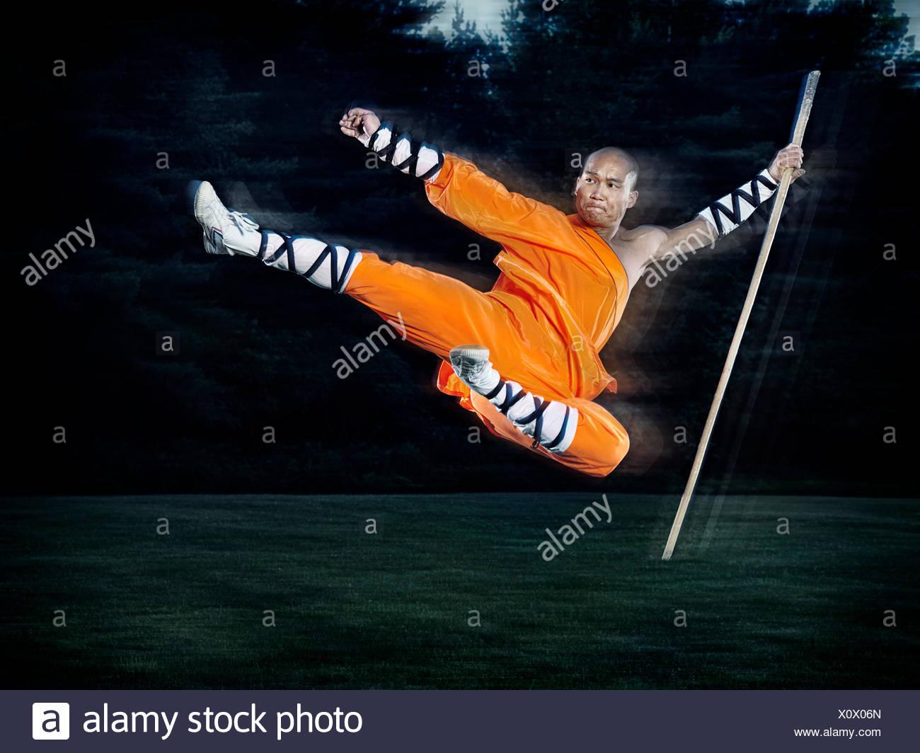 Shaolin Krieger Mönch in der Luft fliegenden Kick springen mit einem Stab im freien Stockbild