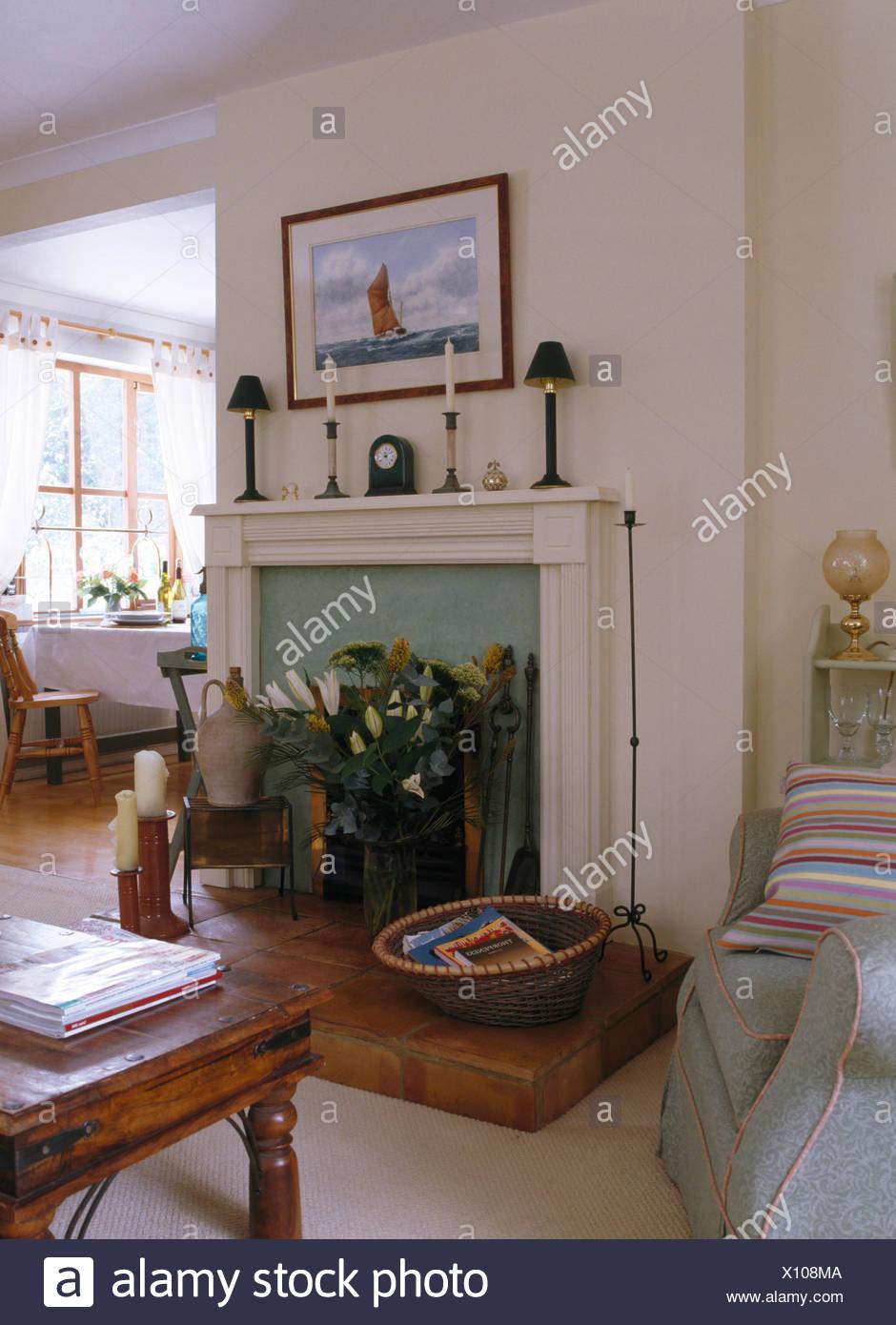 Weiße Wohnzimmer mit Weidenkorb und Vase mit weißen Lilien am Kamin ...