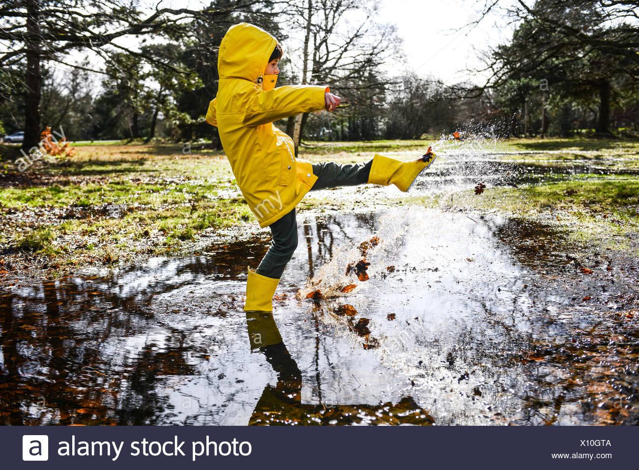 Junge in gelben Anorak planschen im Park Pfütze Stockfoto