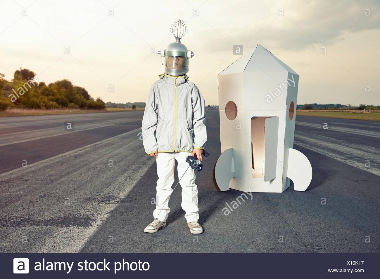 Junge verkleidet als Raumfahrer stehend auf Pappe Rakete Stockbild