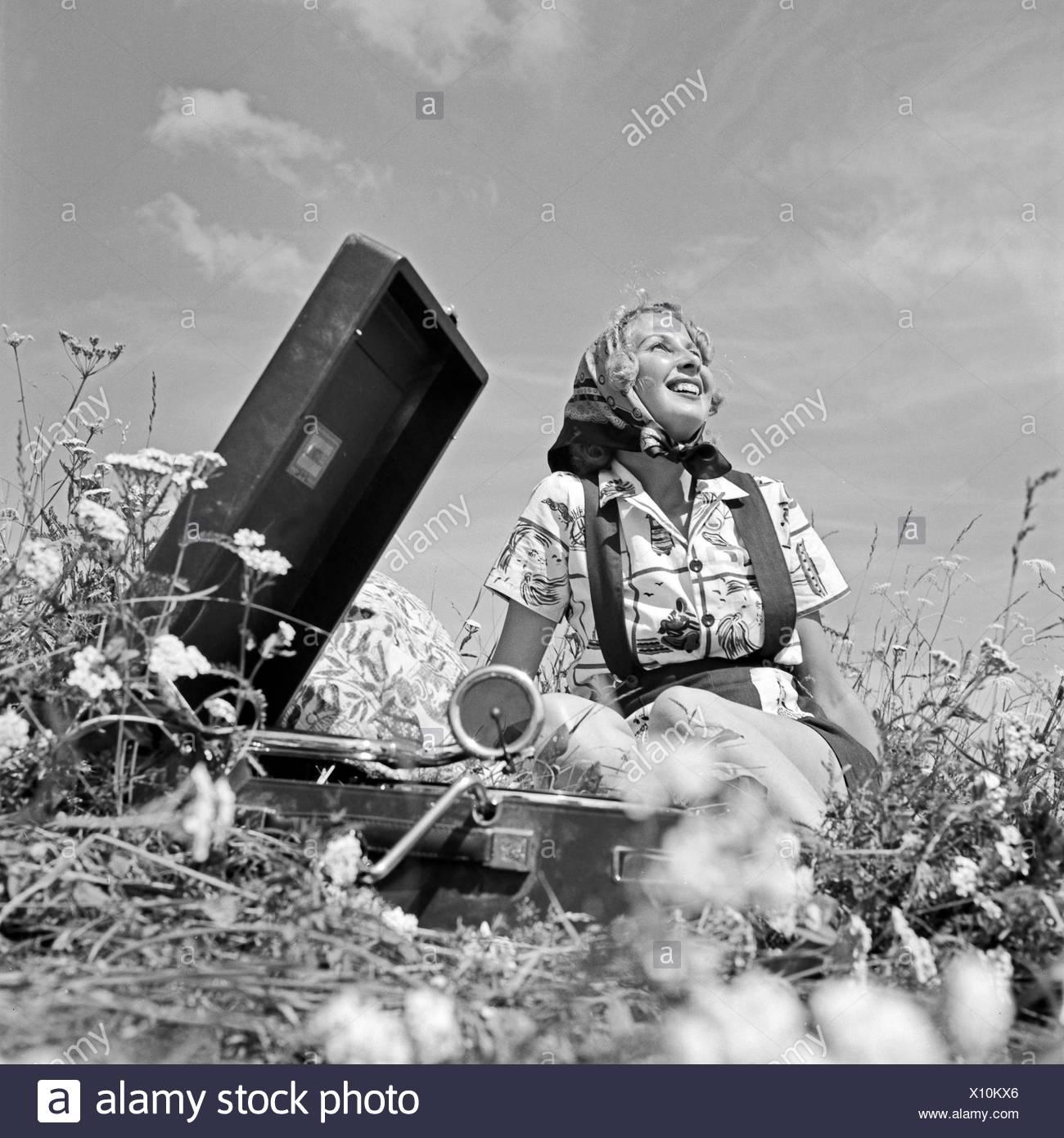 Eine Junge Frau Sitzt Mit Einem Grammophon in Einer Wiese Und Hört Musik, Deutschland, 1930er Jahre. Eine junge Frau in einem Rasen sitzen und hören ein Grammophon, Deutschland der 1930er Jahre. Stockbild