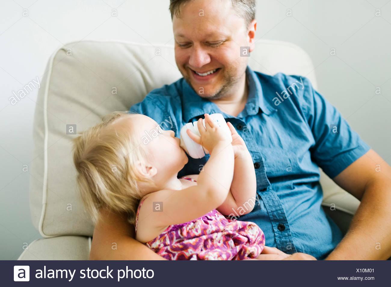 Vater feeding baby girl (12-17 Monate) im Wohnzimmer. Stockfoto