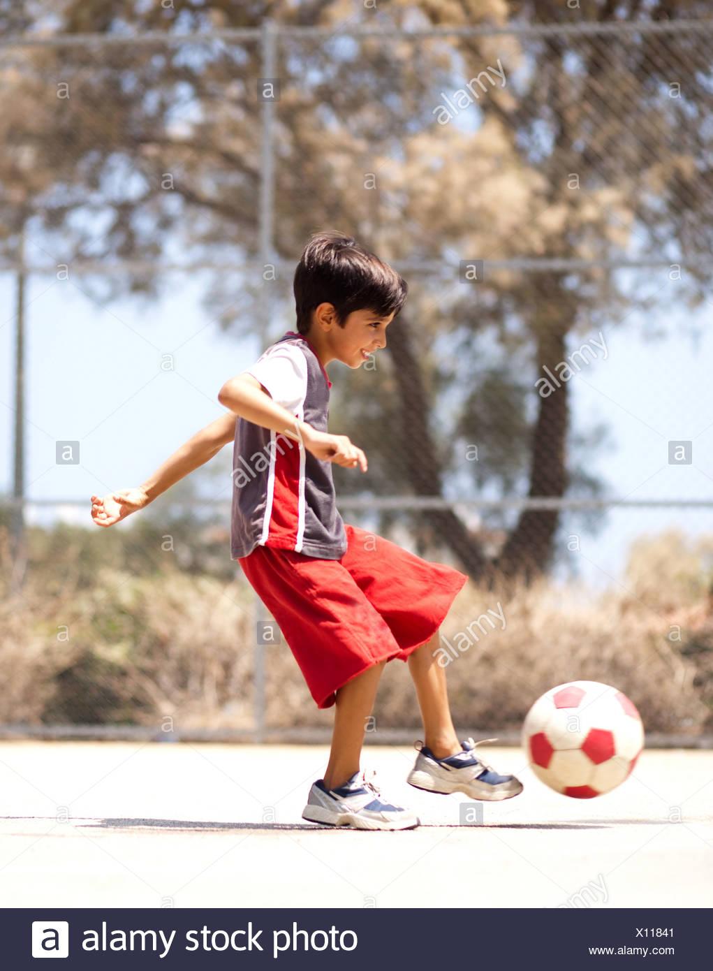 Young kid in Aktion Fußball, im Freien zu genießen Stockbild