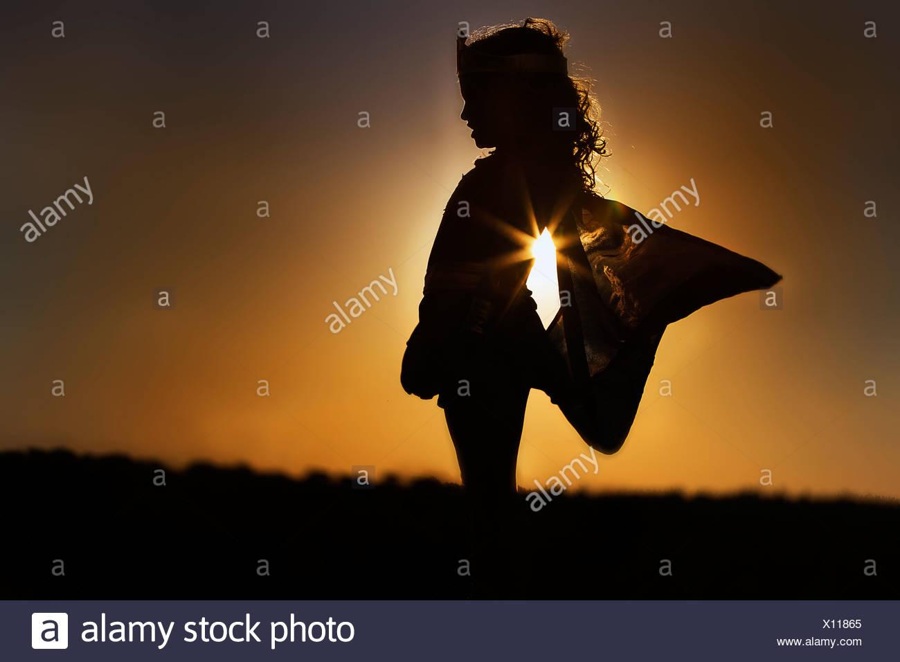 Silhouette eines jungen Mädchens in the Fairy Kostüm bei Sonnenuntergang Stockbild