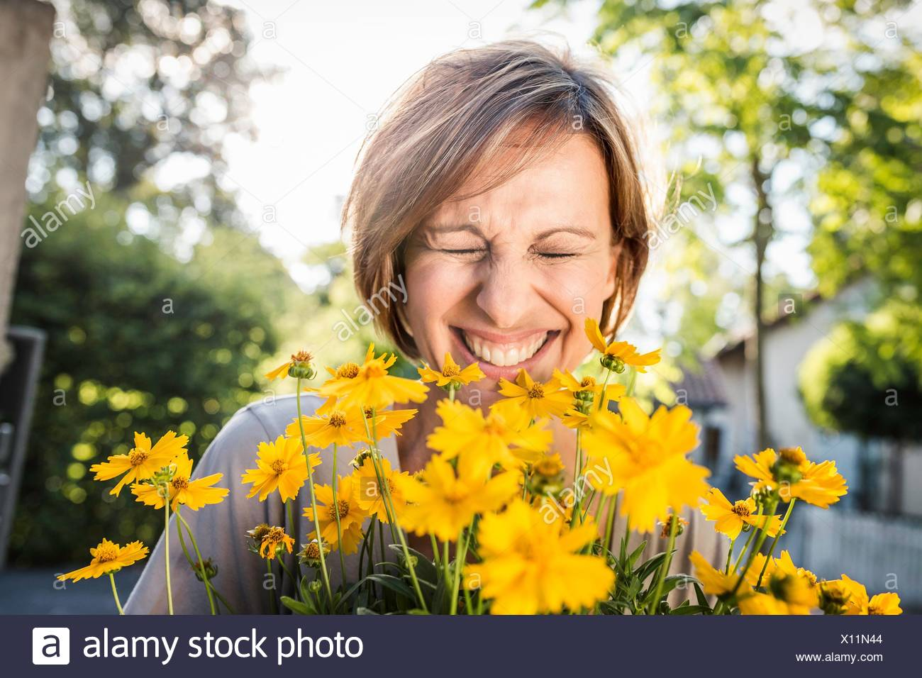 Porträt von Reife Frau mit gelben Blüten Stockbild