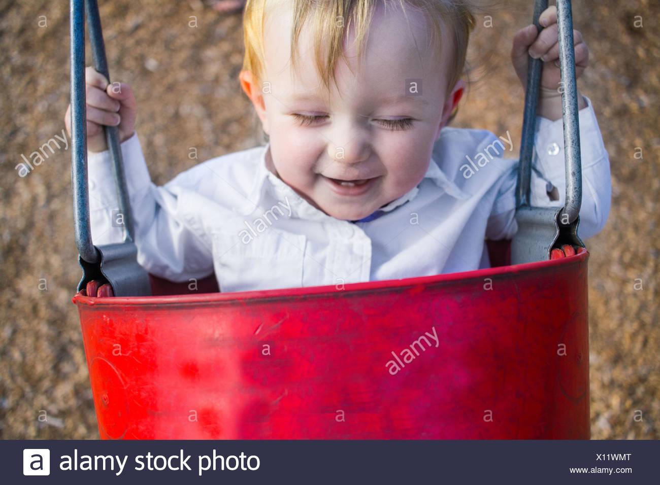 Lächelnde junge sitzt im Eimer Schaukel Stockbild